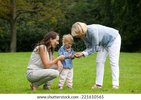 Portrait of a mother and grandmother showing little girl flower - stock photo