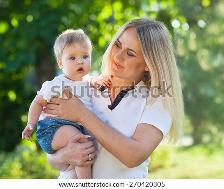 Portrait of a mother and her baby enjoy the summer sunset