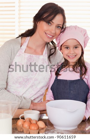 Portrait of a mother and her daughter baking in a kitchen - stock photo