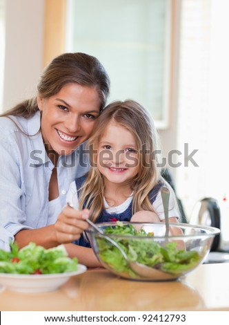 Portrait of a mother and her daughter preparing a salad in their kitchen - stock photo