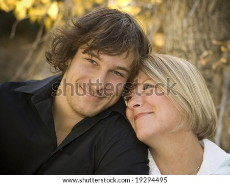 Portrait of a mother and her son. Mom is looking at her son, he's smiling at the camera.