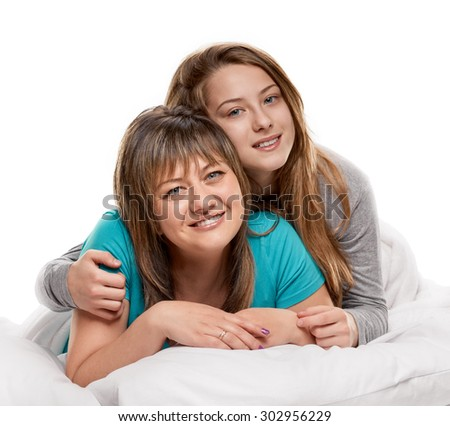 Portrait of a mother and her teenager daughter in the bed on white background