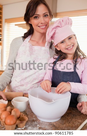 Portrait of a mother baking with her daughter in a kitchen - stock photo
