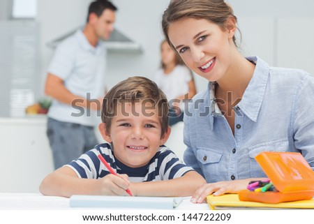 Portrait of a mother drawing with her son while father is discussing with his daughter on the background