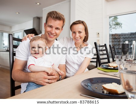 Portrait of a mother father and son after eating in a home interior - stock photo