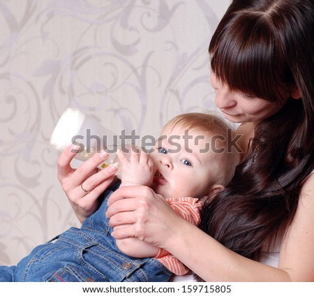 Portrait of a mother feeding baby son from a bottle - stock photo