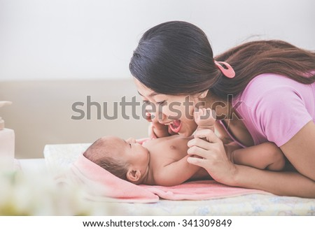 portrait of a mother happily playing with her baby after having bathed - stock photo