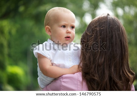 Portrait of a mother holding baby over shoulder outdoors - stock photo