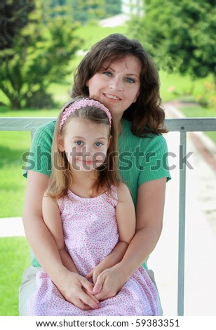 Portrait of a mother in her 40s with her young daughter. - stock photo