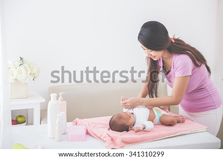 portrait of a mother put on some clothes to her baby - stock photo