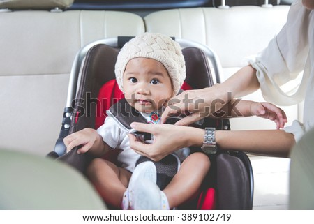 portrait of a Mother securing her baby in the car seat in her car - stock photo