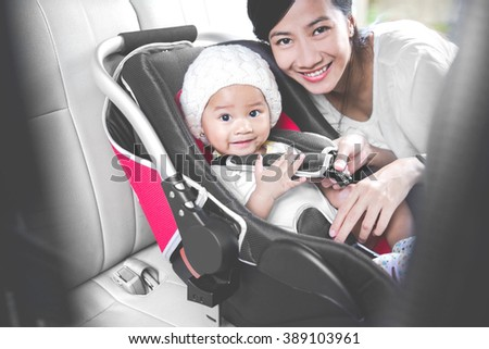 portrait of a Mother securing her baby in the car seat in her car. smiling to camera - stock photo