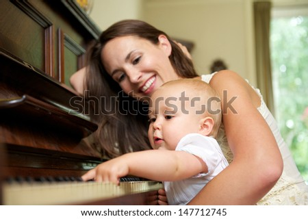 Portrait of a mother smiling as baby plays piano - stock photo