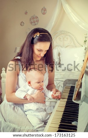 Portrait of a mother with a newborn around the piano - stock photo