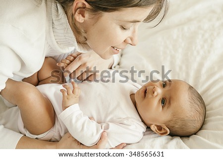 Portrait of a mother with her baby at home. Happy child near to mum in her room.
