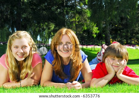 Portrait of a mother with her children lying on the grass in a park - stock photo