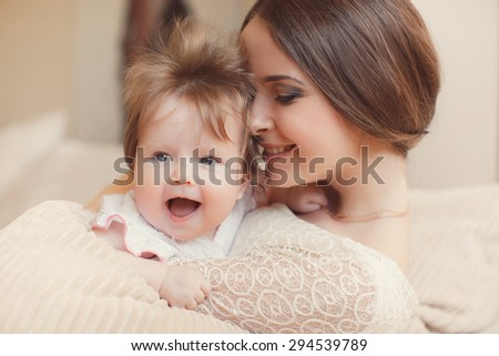Portrait of a mother with her 4 months old baby at home. Happy child near to mum in her room. Portrait of a mother with her newborn baby.