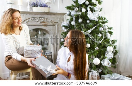Portrait of a mother with teen daughter at home near the Christmas tree being happy and joyful - stock photo