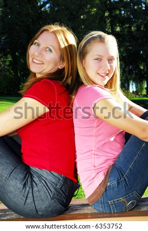 Portrait of a mother with teenage daughter relaxing in summer park - stock photo