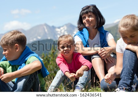 Portrait of a mother with three children outdoors the summer with snow covered mountains in the background - stock photo