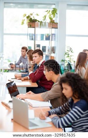 Portrait of a multi ethnic students studying in university library - stock photo