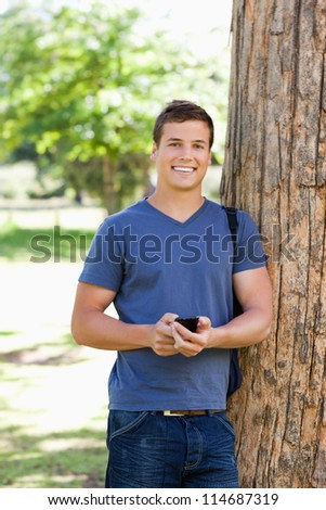Portrait of a muscled young man using a smartphone in a park - stock photo