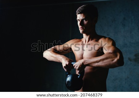 Portrait of a muscular athlete posing with a kettlebell - stock photo