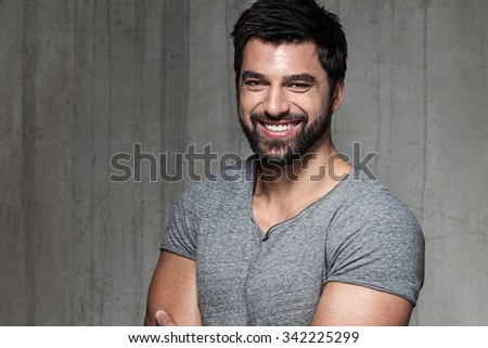 Portrait of a muscular, bearded man in a gray T-shirt