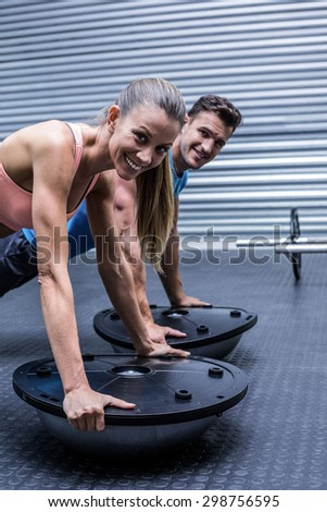 Portrait of a muscular couple doing bosu ball exercises - stock photo