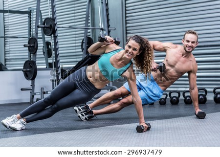 Portrait of a muscular couple doing side plank while lifting weights - stock photo