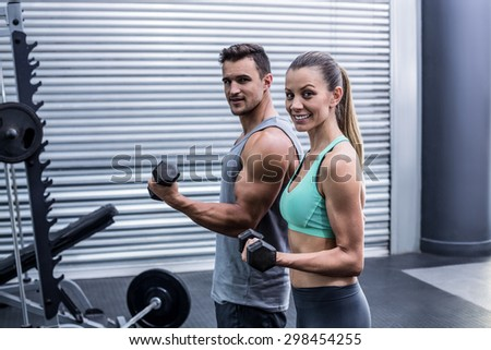Portrait of a muscular couple lifting dumbbells - stock photo
