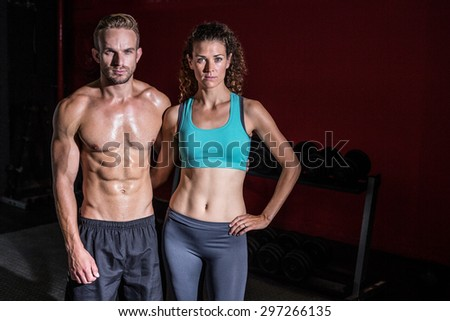 Portrait of a muscular couple on a shadow background - stock photo