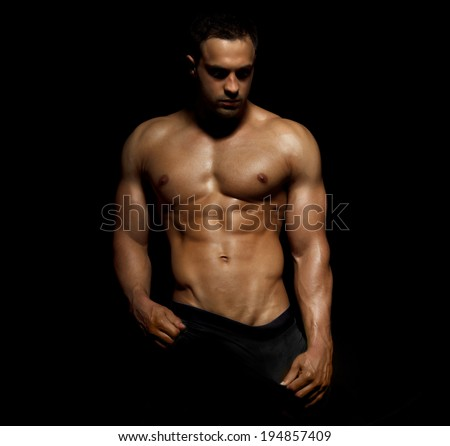 Portrait of a  muscular male model against black background - stock photo