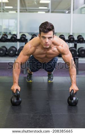 Portrait of a muscular man doing push ups with kettle bells in gym - stock photo