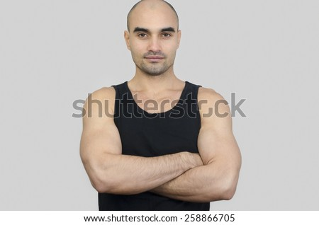 Portrait of a muscular man. Handsome bald man with arms crossed. Fit athletic man in black tank top. - stock photo