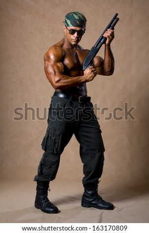 Portrait of a muscular man in a full-length with a gun. - stock photo