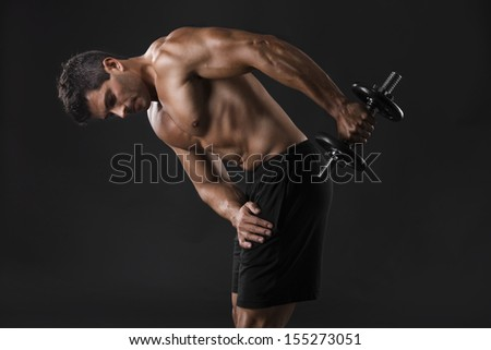Portrait of a muscular man lifting weights against a dark background - stock photo