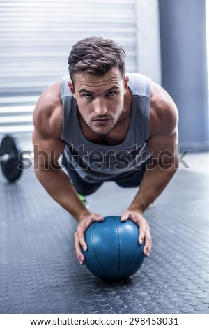 Portrait of a Muscular man on a plank position with a ball - stock photo