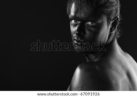 Portrait of a muscular man painted with black color. Body painting project.