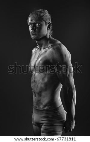 Portrait of a muscular man painted with black color. Body painting project. - stock photo