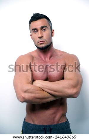 Portrait of a muscular man standing with arms folded  - stock photo