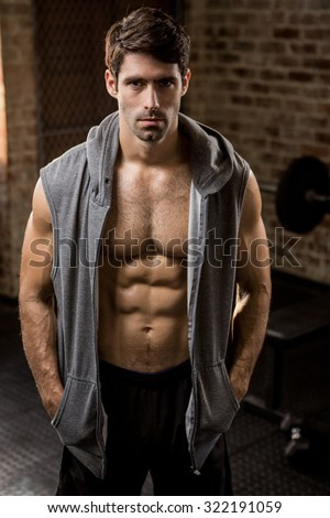 Portrait of a muscular man wearing hood at the gym - stock photo