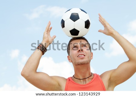 Portrait of a muscular man with football ball on head