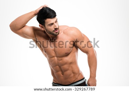 Portrait of a muscular man with naked torso posing isolated on a white background