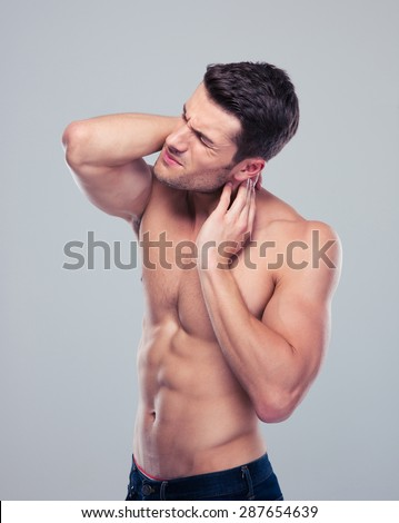 Portrait of a muscular man with neck pain over gray background - stock photo