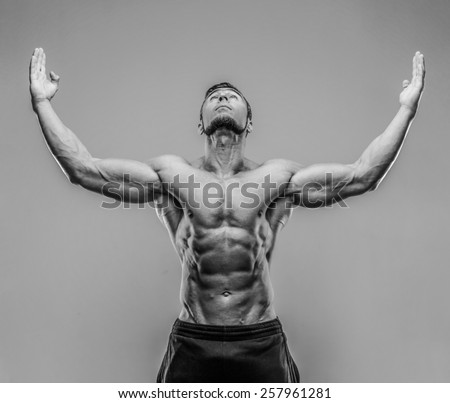 Portrait of a muscular man with raised hands up over gray background. HDR monochrome. - stock photo