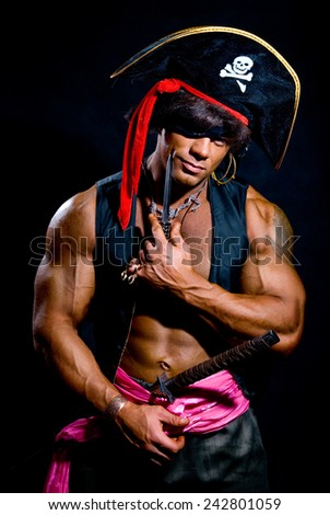 Portrait of a muscular pirate with a knife on a dark background. A man looking at the camera - stock photo
