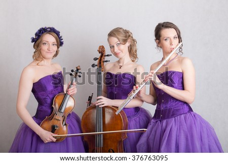 portrait of a musical trio in evening gowns - stock photo
