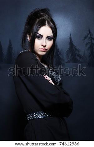 Portrait of a mystical woman in an elegant black dress - stock photo