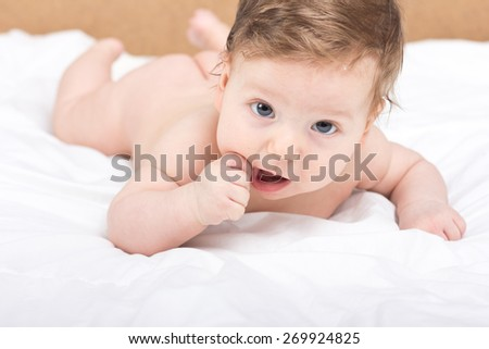 Portrait of a naked child. A child on a white bed. Handsome boy. smiling child